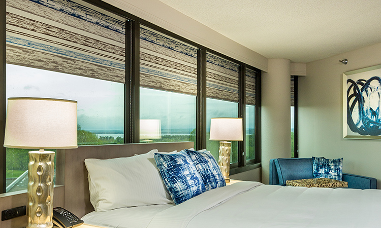 Hotel room featuring roller shades window treatments